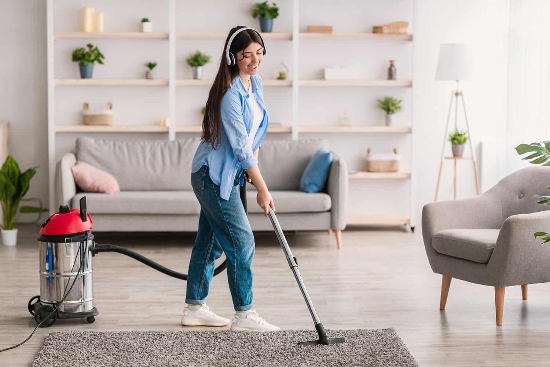 Happy young woman vacuuming rug floor