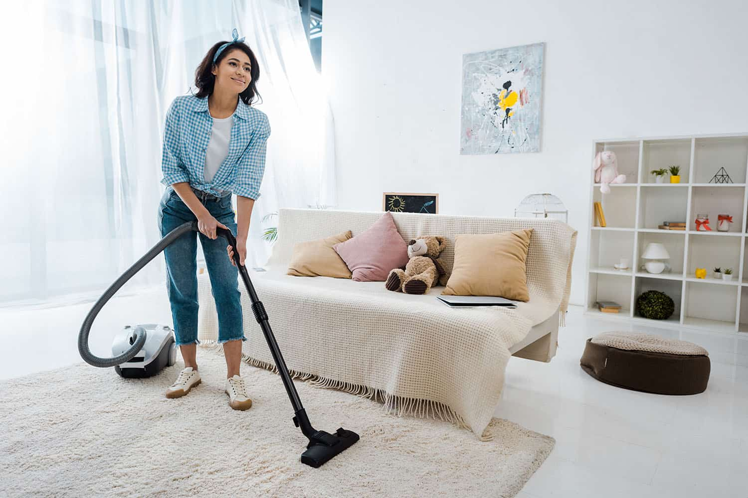 Attractive woman cleaning carpet with vacuum cleaner