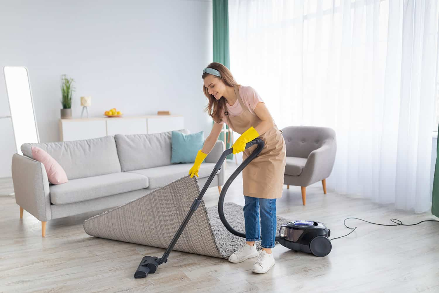 Positive young woman cleaning her apartment