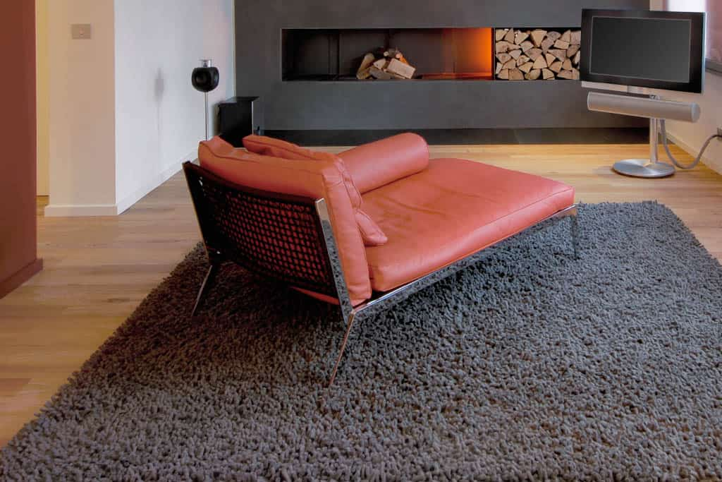 Chaise longue, sofa, fireplace and rug in modern living room
